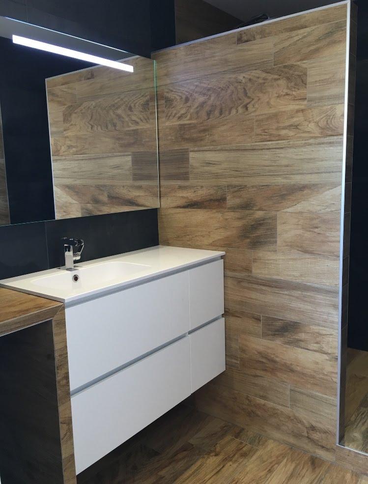 Pose de carrelage mural effet bois dans salle de bains.