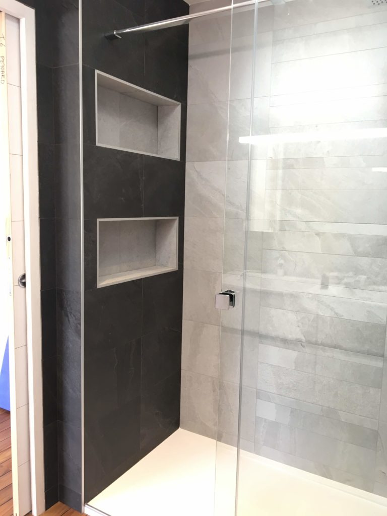 Douche avec étagères incrustées dans le mur.
