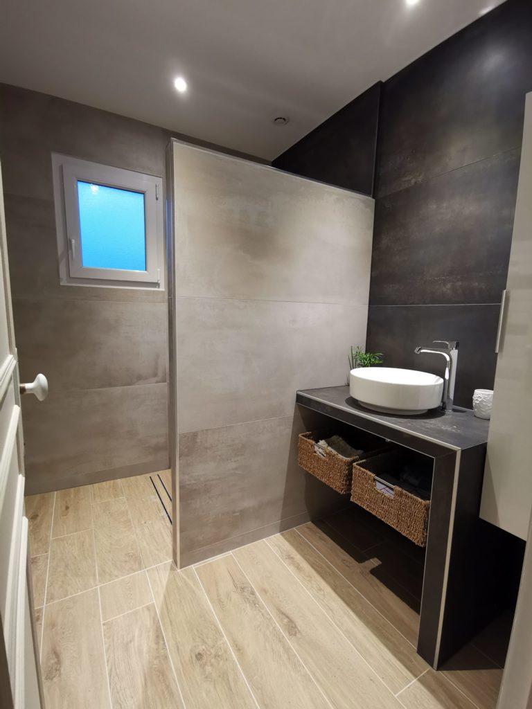 Aménagement d'une salle de bain avec grands carreaux et douche à l'italienne