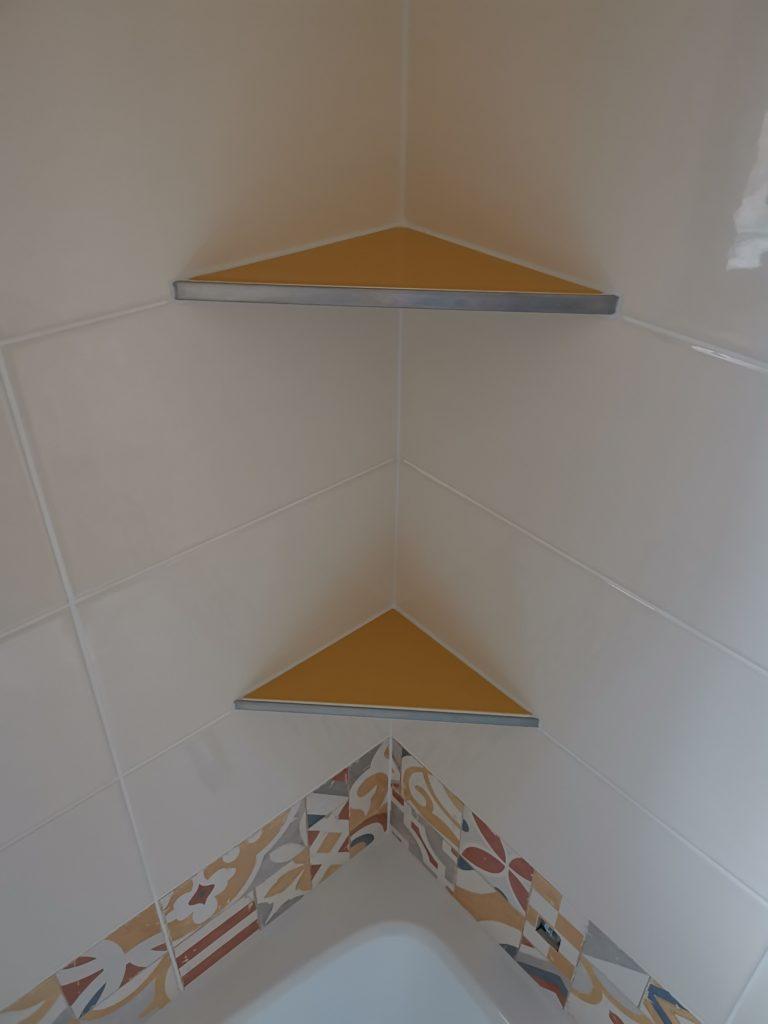 Pose de carrelage jaune et blanc avec frise dans salle de bains avec étagères de coins