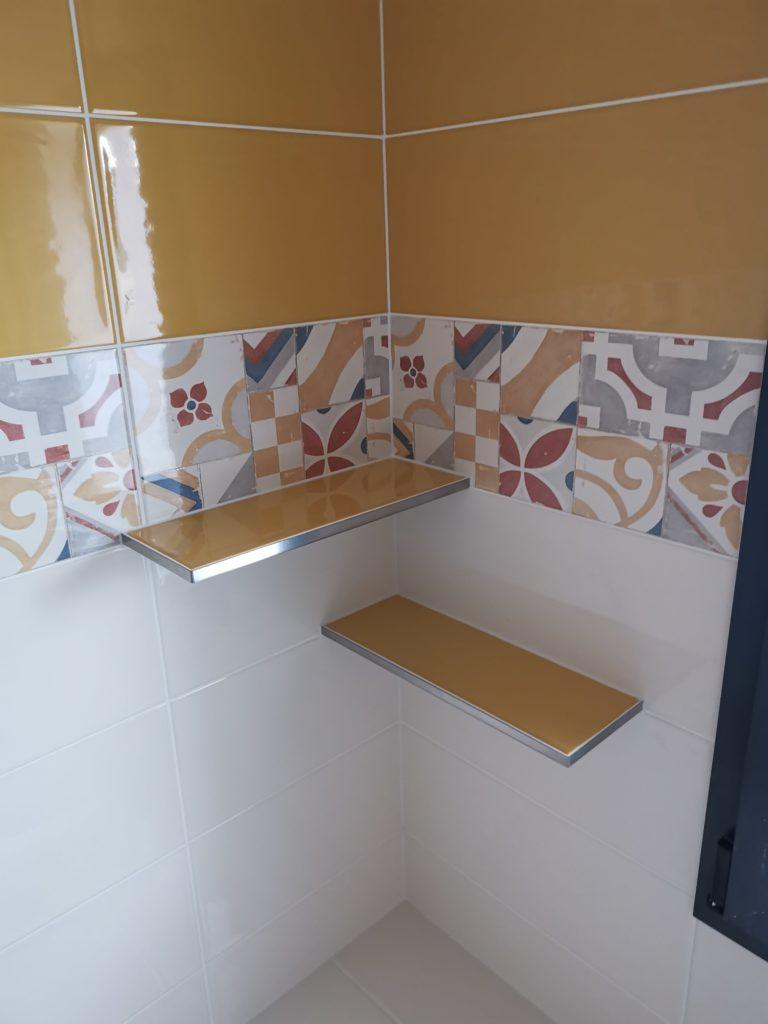 Pose de carrelage jaune et blanc avec frise dans salle de bains avec étagères