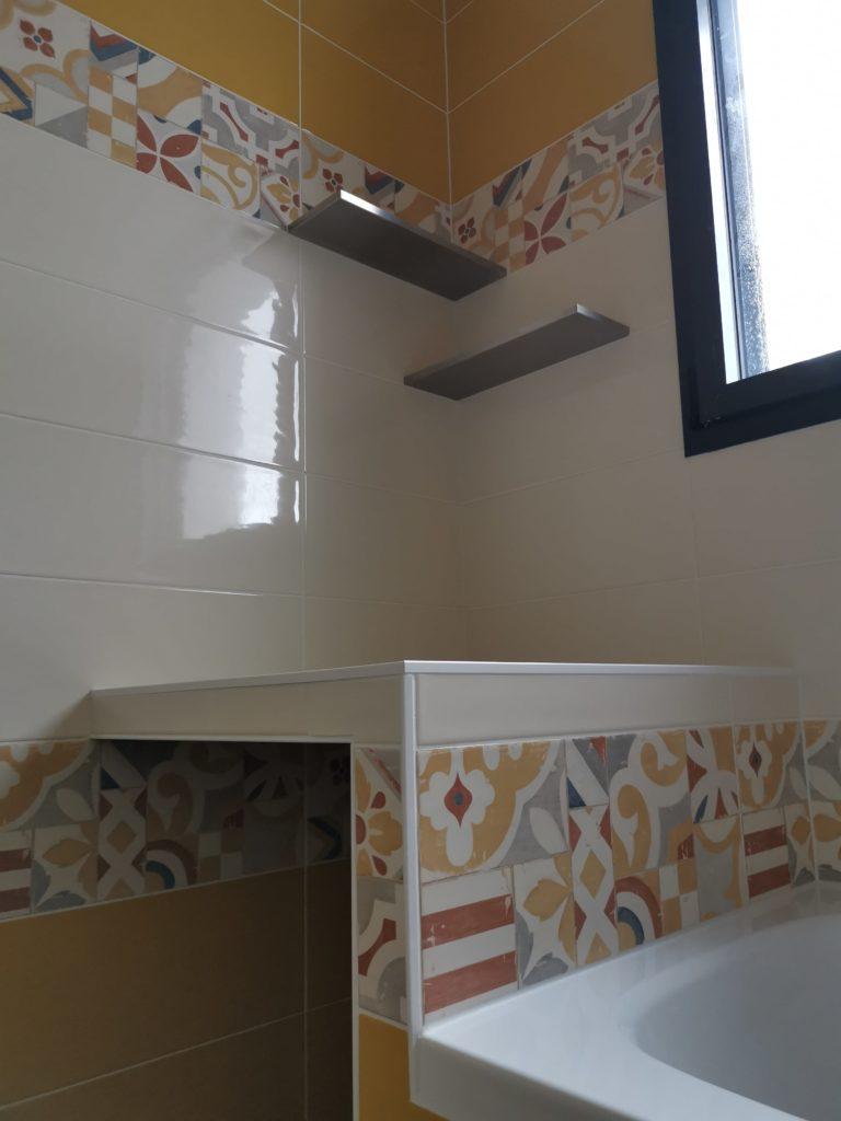 Pose de carrelage jaune et blanc avec frise dans salle de bains avec tablette incrustée dans le mur