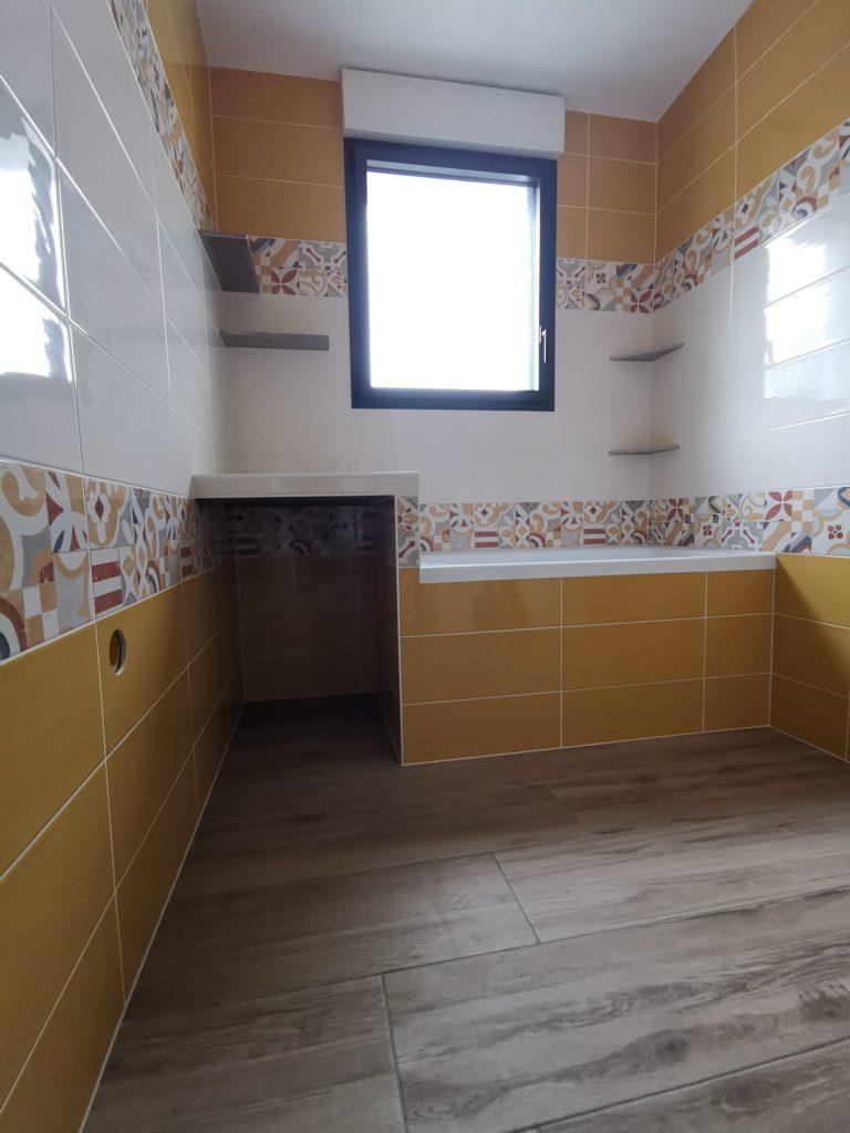 Pose de carrelage jaune et blanc avec frise dans salle de bains