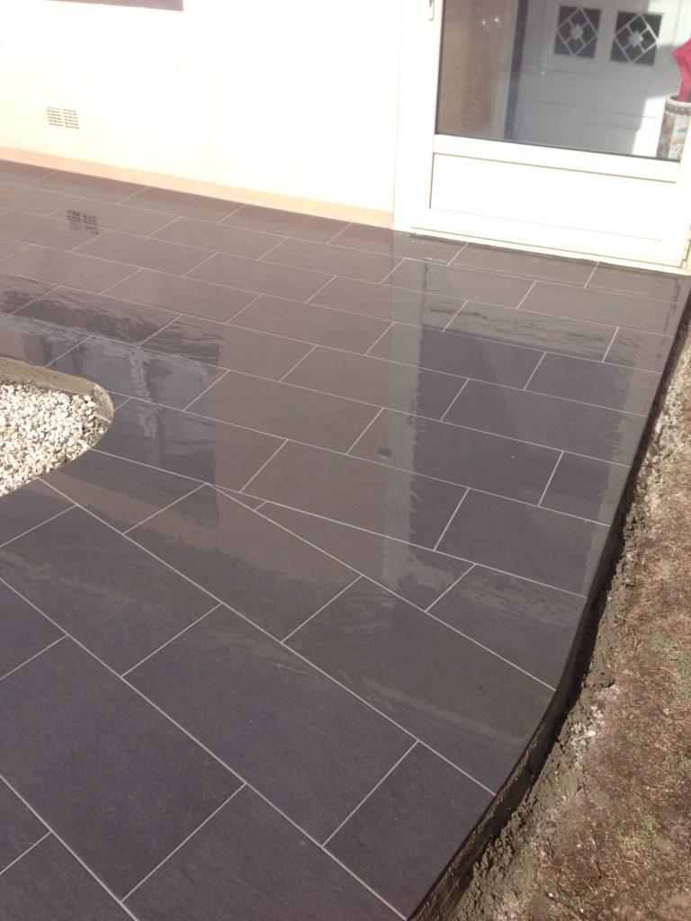 Terrasse en carrelage noir extérieur avec angle arrondi.