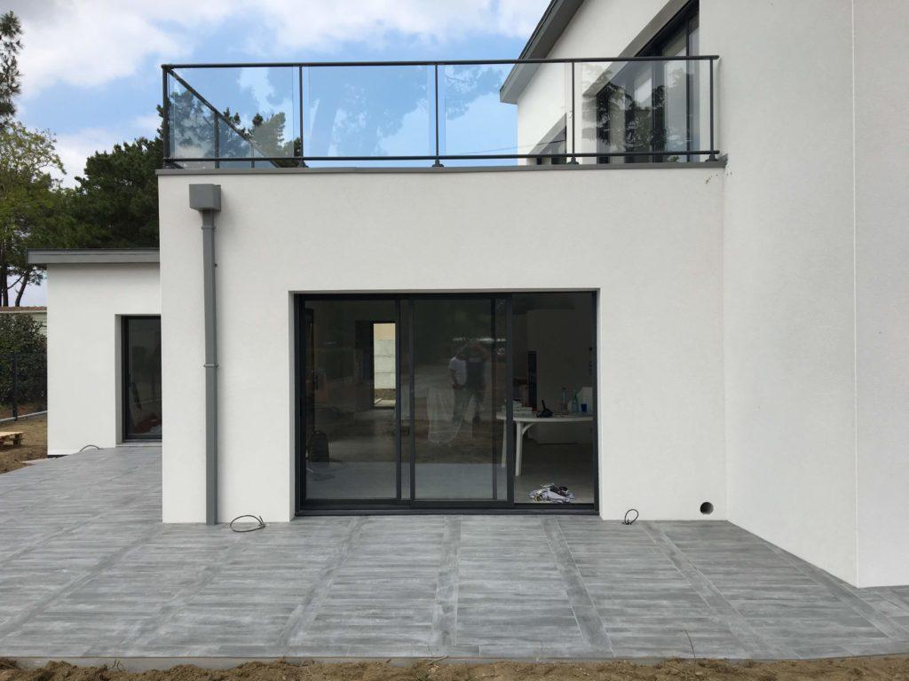 Pose d'une terrasse extérieure autour d'une maison moderne.