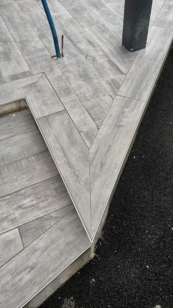 Découpe d'un coin sur terrasse en carrelage effet bois.