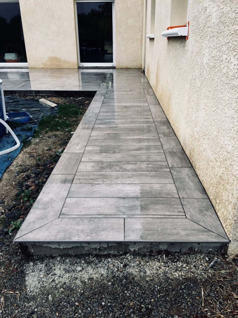 Terrasse grise avec carreaux effet bois.