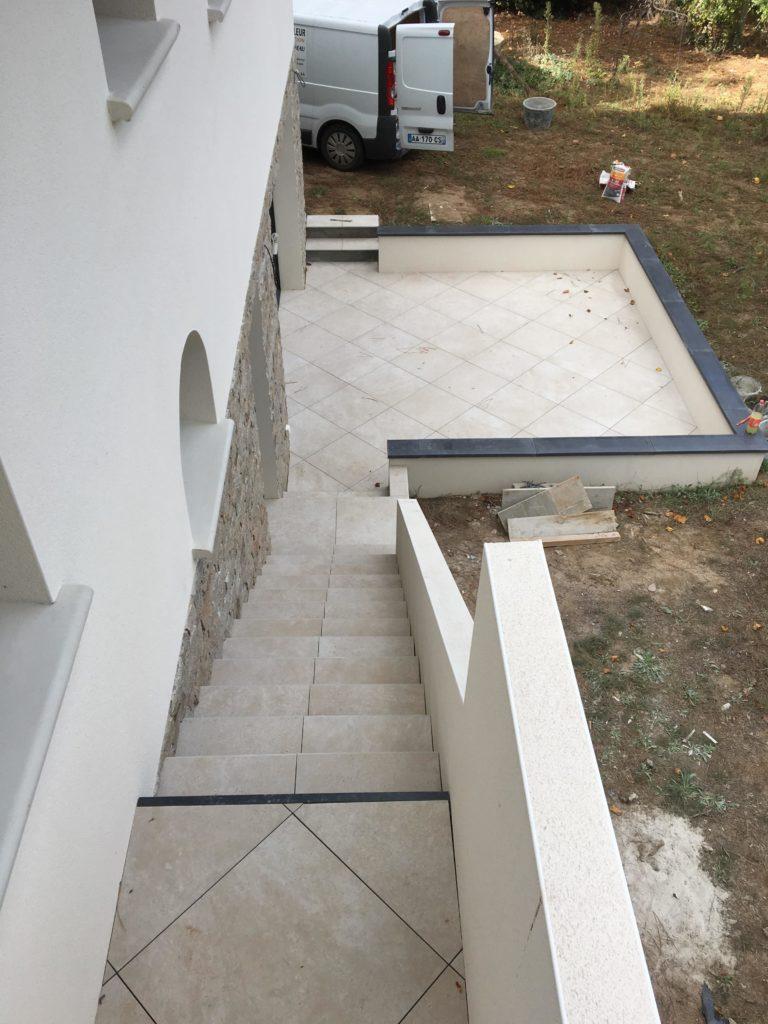 Aménagement extérieur avec escalier en pierre et terrasse en dalles.